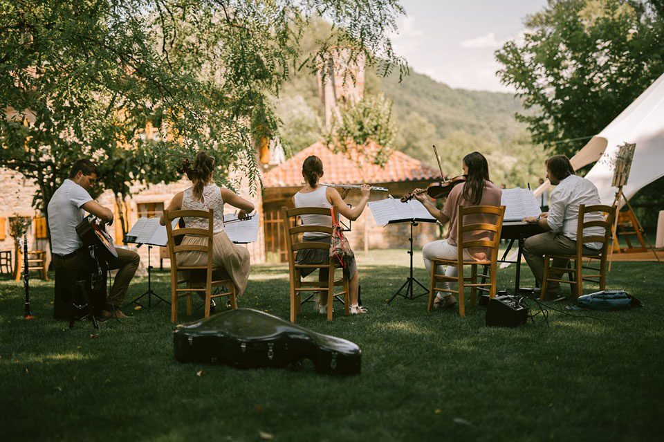 Band playing acoustic music outdoors at Lake Bled Wedding